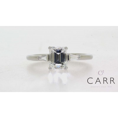EMERALD CUT CENTRE THREE STONE RING